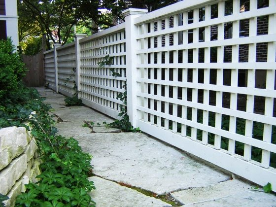 long-and-firm-white-lattice-fence-design-with-concrete-patio-design-with-greenery-beneath-shady-tree