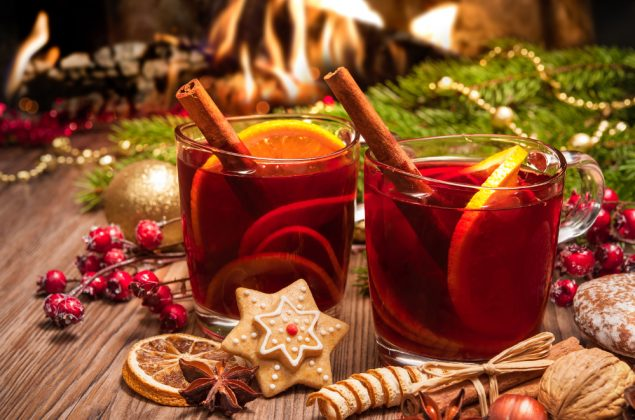 Christmas Punch - Two glasses of mulled wine with christmas decoration at romantic fireplace