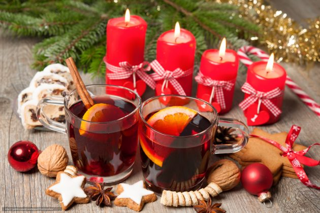 Christmas Punch - Red mulled wine on table with burning candles